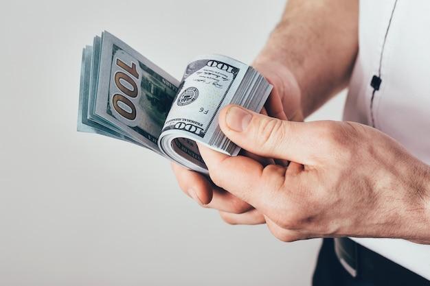 Geschäftsmann hält geld in händen. männlich zählt das einkommen. geld ist in dollarnoten gestapelt.