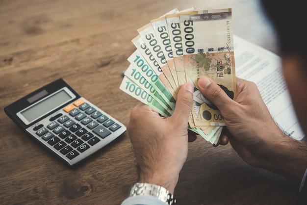 Geschäftsmann hält geld, südkorea gewann rechnungen am arbeitstisch
