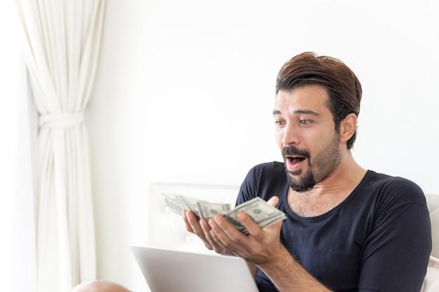 Geschäftsmann hält geld us-dollar-scheine im home office