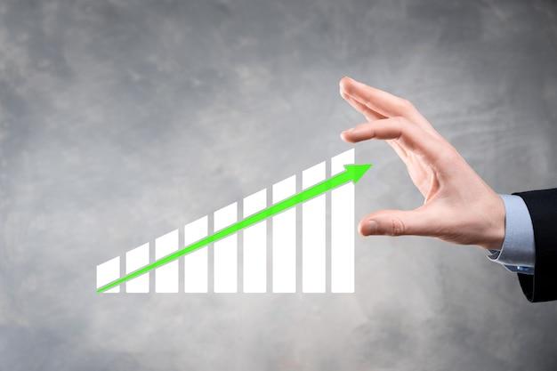 Geschäftsmann hält grafikwachstum und zunahme von chart-positiven indikatoren in seinem geschäft. investment-up-konzept. analyse von verkaufsdaten und wirtschaft, strategie und planung, digitales marketing und aktien