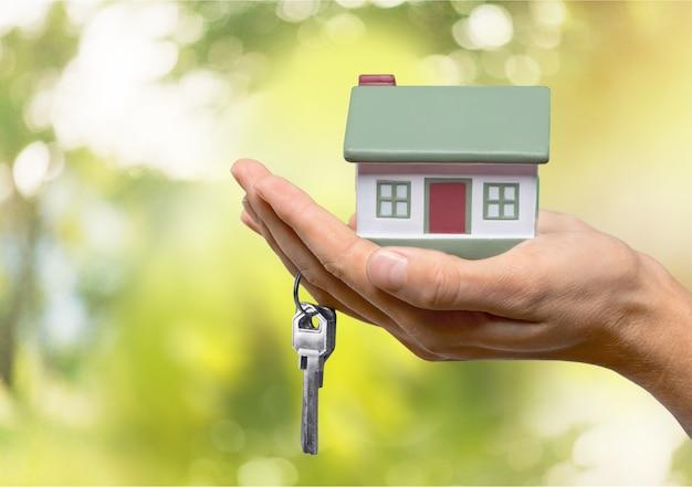 Geschäftsmann hält hausmodell und schlüssel, immobilienkonzept