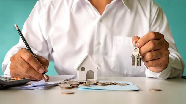 Geschäftsmann hält hausschlüssel und haus entwirft finanzkonzept hypothek und real estate mortgage