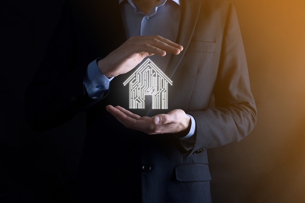 Geschäftsmann hält haussymbol. smart home gesteuertes, intelligentes haus und hausautomatisierungs-app-konzept. pcb-design und person mit smartphone. innovation-technologie-internet-netzwerk-konzept.