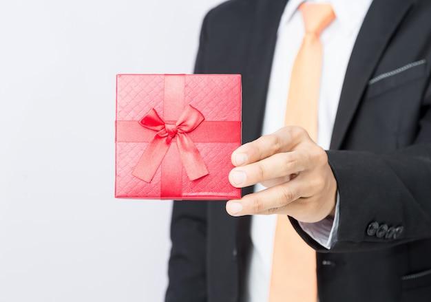 Geschäftsmann hält heraus den geschenkrotkasten