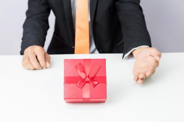 Geschäftsmann hält heraus den roten kasten des geschenks, lokalisierten hintergrund