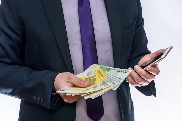 Geschäftsmann hält in einer hand euro und ein anderes telefon
