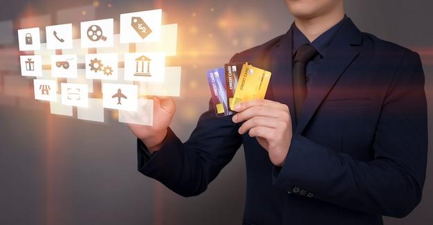 Geschäftsmann hält kreditkarte und analysiert bankfinanzdaten auf digitalem virtuellem bildschirm