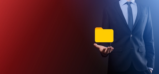 Geschäftsmann hält ordnersymbol. dokumentenverwaltungssystem oder dms-setup durch einen it-berater mit einem modernen computer suchen die verwaltung von informationen und unternehmensdateien. geschäftsverarbeitung,