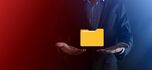 Geschäftsmann hält ordnersymbol. dokumentenverwaltungssystem oder dms-setup durch einen it-berater mit einem modernen computer suchen nach informationen und unternehmensdateien