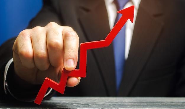 Geschäftsmann hält pfeil hoch. konzept der erfolgreichen entwicklung von wirtschaft und wirtschaft.