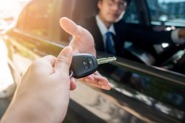 Geschäftsmann hält schlüsselauto im auto