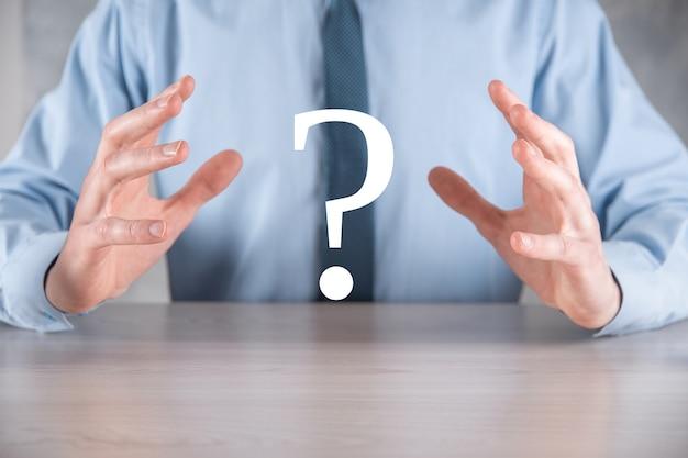 Geschäftsmann hält schnittstelle fragezeichen zeichen web. fragen sie online, faq-konzept, was wo wann wie und warum, suchen sie informationen im internet.