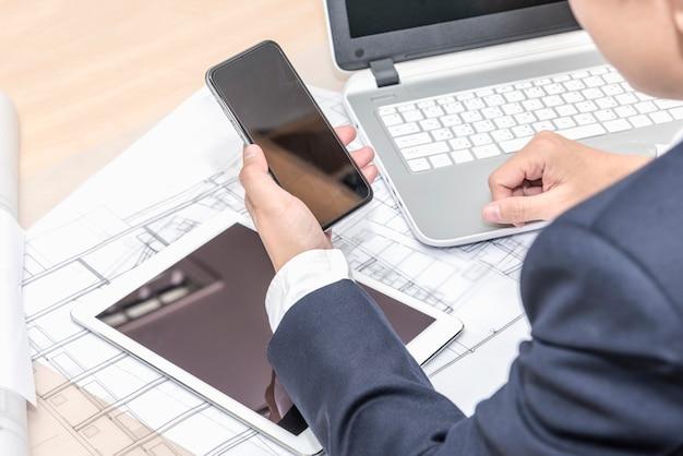 Geschäftsmann hält smartphone über tablet pc computer blaupause