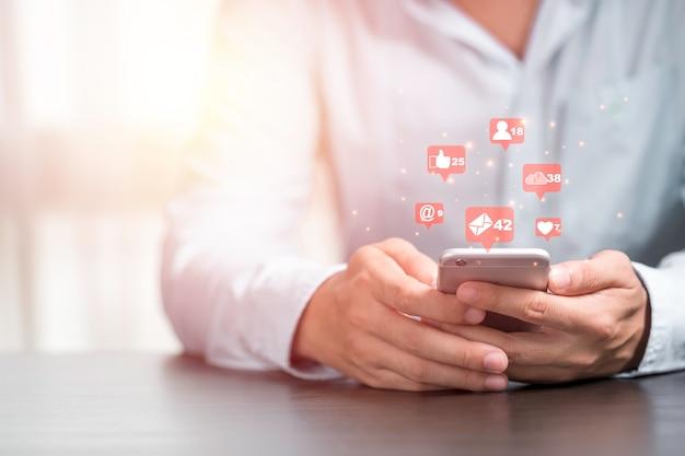 Geschäftsmann hält smartphone, um social-media-symbol wie liebe wie und stern zu verwenden. marketing- und geschäftskonzept.