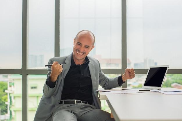 Geschäftsmann hält stiftlächeln im büro, geschäftsmann lächelt glücklich, händler-online-kryptowährungserfolg