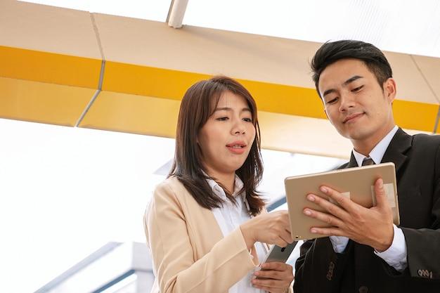 Geschäftsmann hält tablette mit frau zeigt auf daten