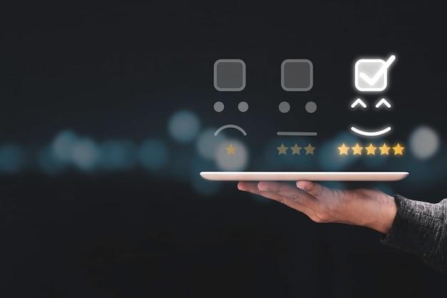 Geschäftsmann hält tablette und zeigt kunden online-bewertungsergebnis für fünf sterne.