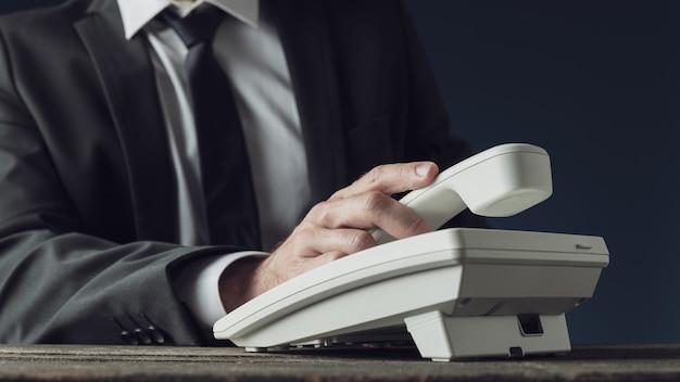 Geschäftsmann hält telefonhörer