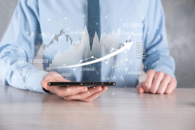 Geschäftsmann hält verkaufsdaten und wirtschaftswachstumsdiagramm. unternehmensplanung und strategie. analyse des börsenhandels. finanz- und bankwesen. digitales marketing der technologie. profit und wachstumsplan.