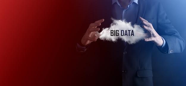 Geschäftsmann hält wolke mit aufschrift, wort big data. symbol. auf dunklem hintergrund.