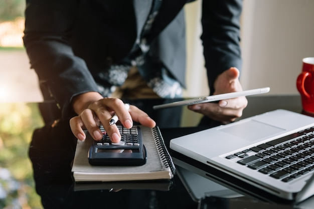 Geschäftsmann hände arbeiten mit finanzen über kosten und rechner und laptop mit tablet, smartphone im büro im morgenlicht