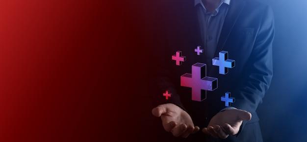 Geschäftsmann halten 3d plus-symbol, mann halten in der hand bieten positive dinge wie gewinn, nutzen, entwicklung, csr durch pluszeichen dargestellt. die hand zeigt das pluszeichen.