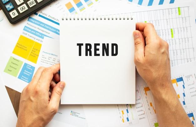 Geschäftsmann halten notizblock mit text trend. finanzdiagramme auf dem desktop