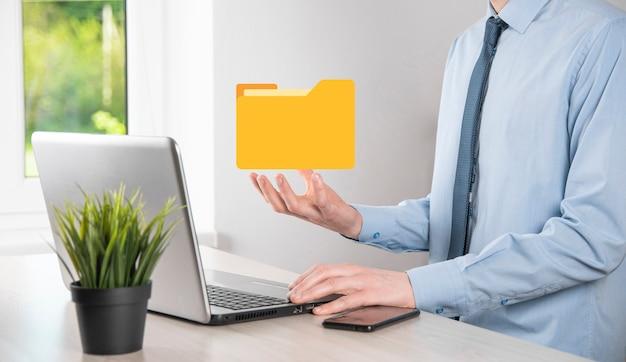 Geschäftsmann halten ordnersymbol. dokumentenverwaltungssystem oder dms-setup durch it-berater mit modernem computer suchen nach der verwaltung von informationen und unternehmensdateien.