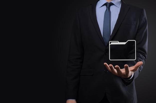 Geschäftsmann halten ordnersymbol. dokumentenverwaltungssystem oder dms-setup durch it-berater mit modernem computer suchen nach verwaltungsinformationen und unternehmensdateien. geschäftsverarbeitung,