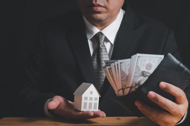 Geschäftsmann halten papierhausmodell und überprüfen sie geld in der brieftasche