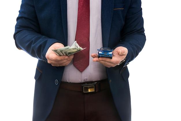 Geschäftsmann halten spielzeugauto und uns geld zum verkauf oder mietwagen isoliert auf weiß