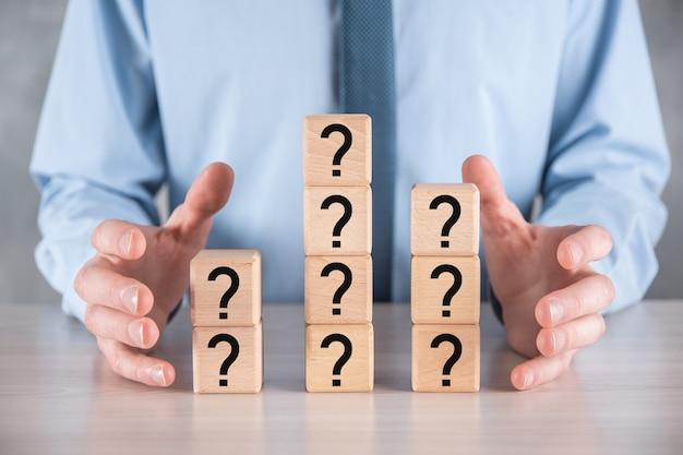 Geschäftsmann halten und setzen hölzerne würfelblockform mit fragezeichen auf grauem tisch. platz für text.concept für verwirrung, frage oder lösung.