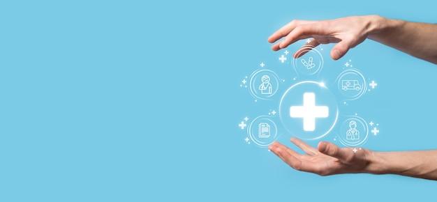 Geschäftsmann halten virtuelle plus medizinische netzwerkverbindungssymbole. die covid-19-pandemie entwickelt das bewusstsein der menschen und lenkt die aufmerksamkeit auf ihre gesundheitsversorgung. arzt, dokument, medizin, krankenwagen, patientensymbol.