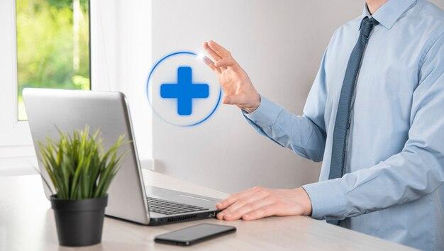 Geschäftsmann halten virtuelle plus medizinische netzwerkverbindungssymbole. die covid-19-pandemie fördert das bewusstsein der menschen und macht auf ihre gesundheitsversorgung aufmerksam.