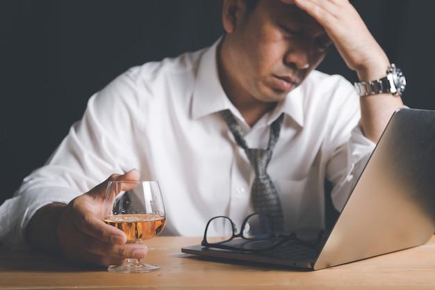 Geschäftsmann halten whiskyglas und fühlen sich gestresst