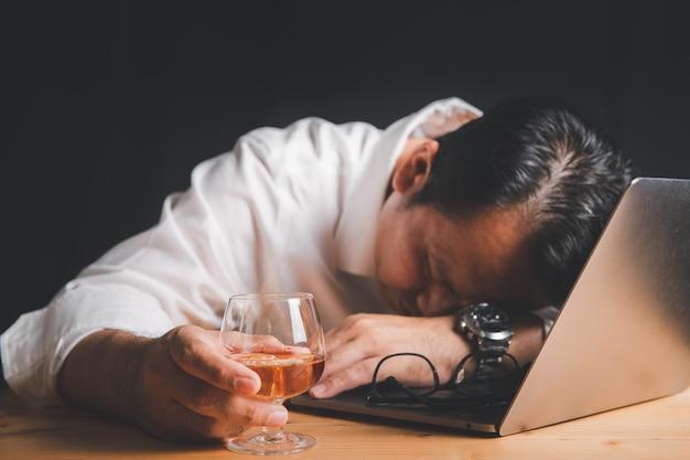 Geschäftsmann halten whiskyglas und schlafen auf laptop