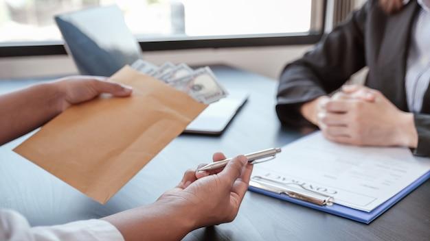 Geschäftsmann hand bieten bestechungsgelder in umschlag für die unterzeichnung eines vertrags von geschäftsprojekt
