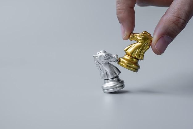 Geschäftsmann hand, der goldschachritter (pferd) bewegt