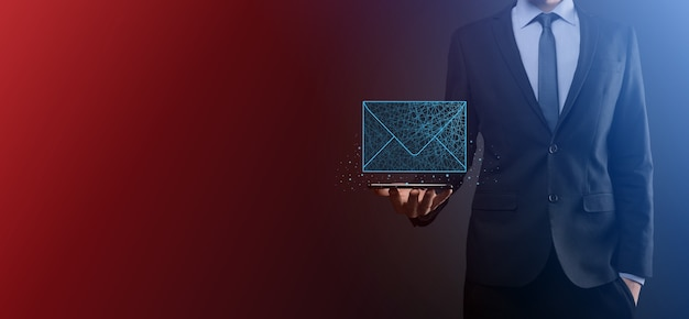 Geschäftsmann hand, die briefsymbol, e-mail-symbole hält. kontaktieren sie uns per newsletter-e-mail und schützen sie ihre persönlichen daten vor spam-mail. kundendienst-callcenter kontaktieren sie uns. e-mail-marketing-newsletter.