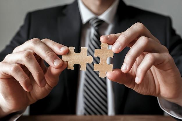 Geschäftsmann hand, die puzzle verbindet