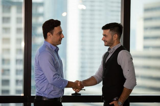 Geschäftsmann hand gegen stadtgebäude schütteln