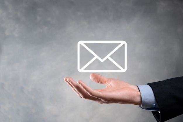 Geschäftsmann hand hält e-mail-symbol, kontaktieren sie uns per newsletter-e-mail und schützen sie ihre persönlichen daten vor spam-mail. kundendienst call center kontaktieren sie uns konzept.