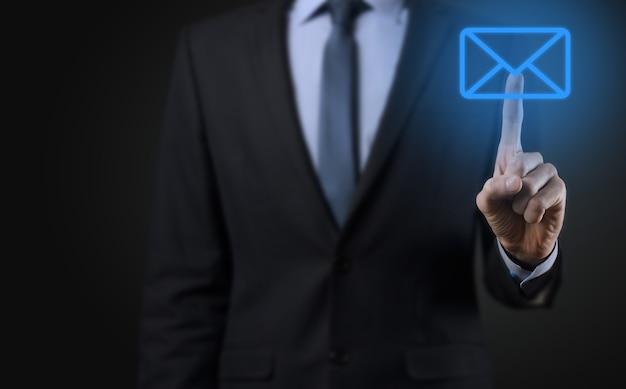 Geschäftsmann hand hält e-mail-symbol, kontaktieren sie uns per newsletter-e-mail und schützen sie ihre persönlichen daten vor spam-mail
