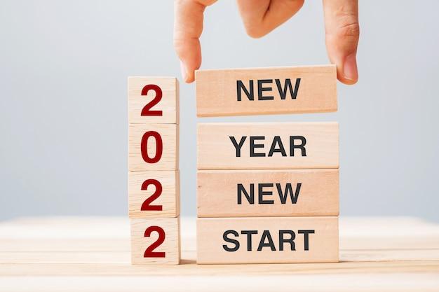 Geschäftsmann hand hält holzblock mit text 2022 neues jahr neustart auf tabellenhintergrund. auflösung, strategie, lösung, geschäfts- und urlaubskonzepte