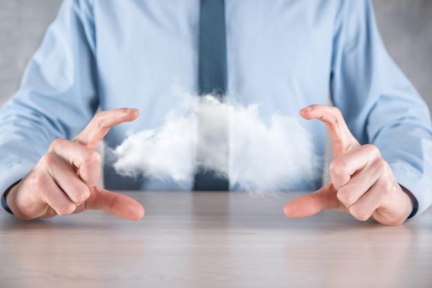 Geschäftsmann hand hält wolke. cloud computing-konzept, nahaufnahme des jungen geschäftsmannes mit wolke über seiner hand. das konzept des cloud-dienstes.