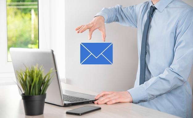 Geschäftsmann hand mit e-mail-symbol, kontaktieren sie uns per newsletter-e-mail und schützen sie ihre persönlichen daten vor spam-mails kundenservice-callcenter kontaktieren sie uns konzept.