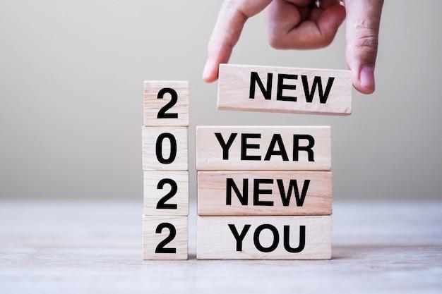 Geschäftsmann hand mit holzwürfel mit text 2022 new year new you auf tabellenhintergrund. auflösung, strategie, lösung, ziel, geschäfts- und urlaubskonzepte