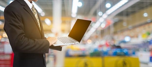 Geschäftsmann hand mit laptop in unschärfe supermarkt und einzelhandel im einkaufszentrum hintergrund