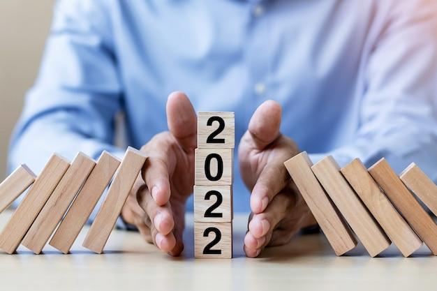 Geschäftsmann hand stopping falling von 2022 holzklötzen. business, risk management, insurance, resolution, strategie, solution, goal, new year new you und happy holiday konzepte