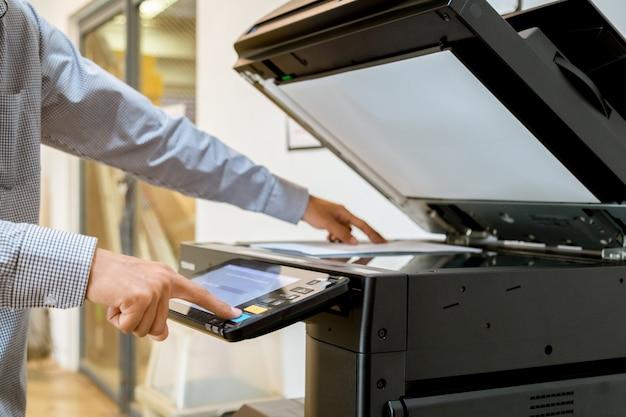 Geschäftsmann handpresseknopf auf platte des druckers, druckerscanner-laser-bürokopie-maschinenversorgungen beginnen